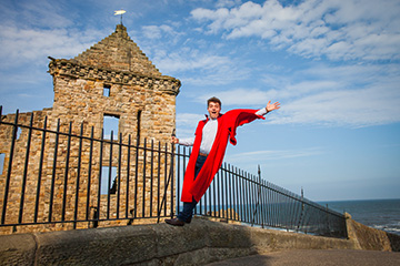 Student in red gown holding railings