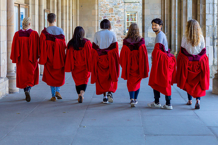 Students in red gowns looking back