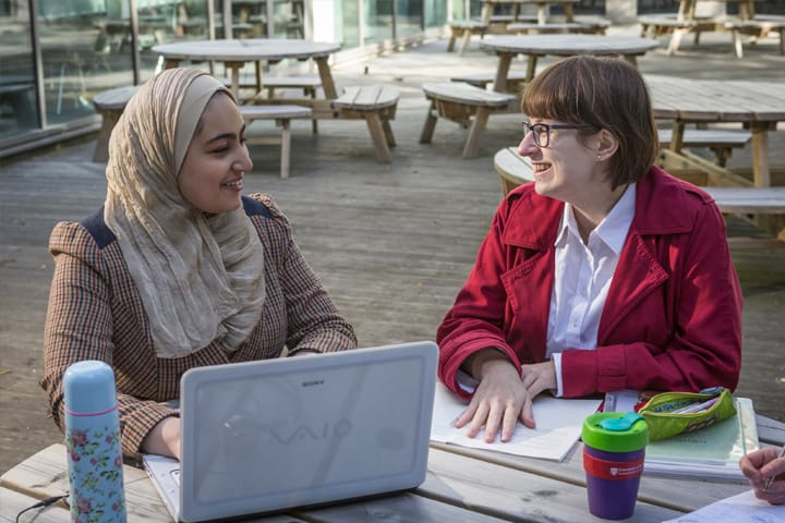 Two students talking outside at a desk