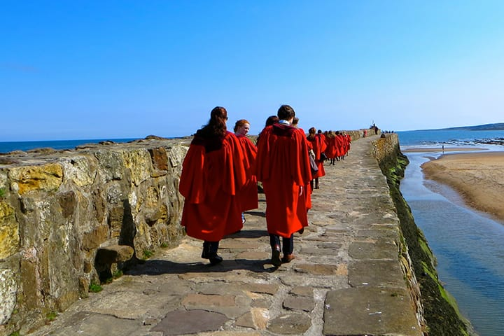 Students wearing red gowns walking down the pier