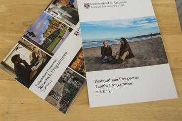 Two University prospectus books lying on a desk