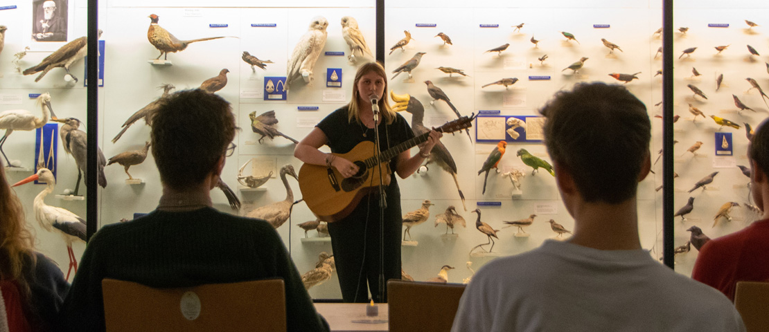 A young singer-songwriter performs with her guitar in front of an audience in the Bell Pettigrew Museum.