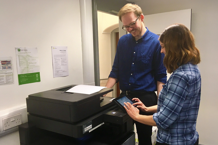 Two people using University printers