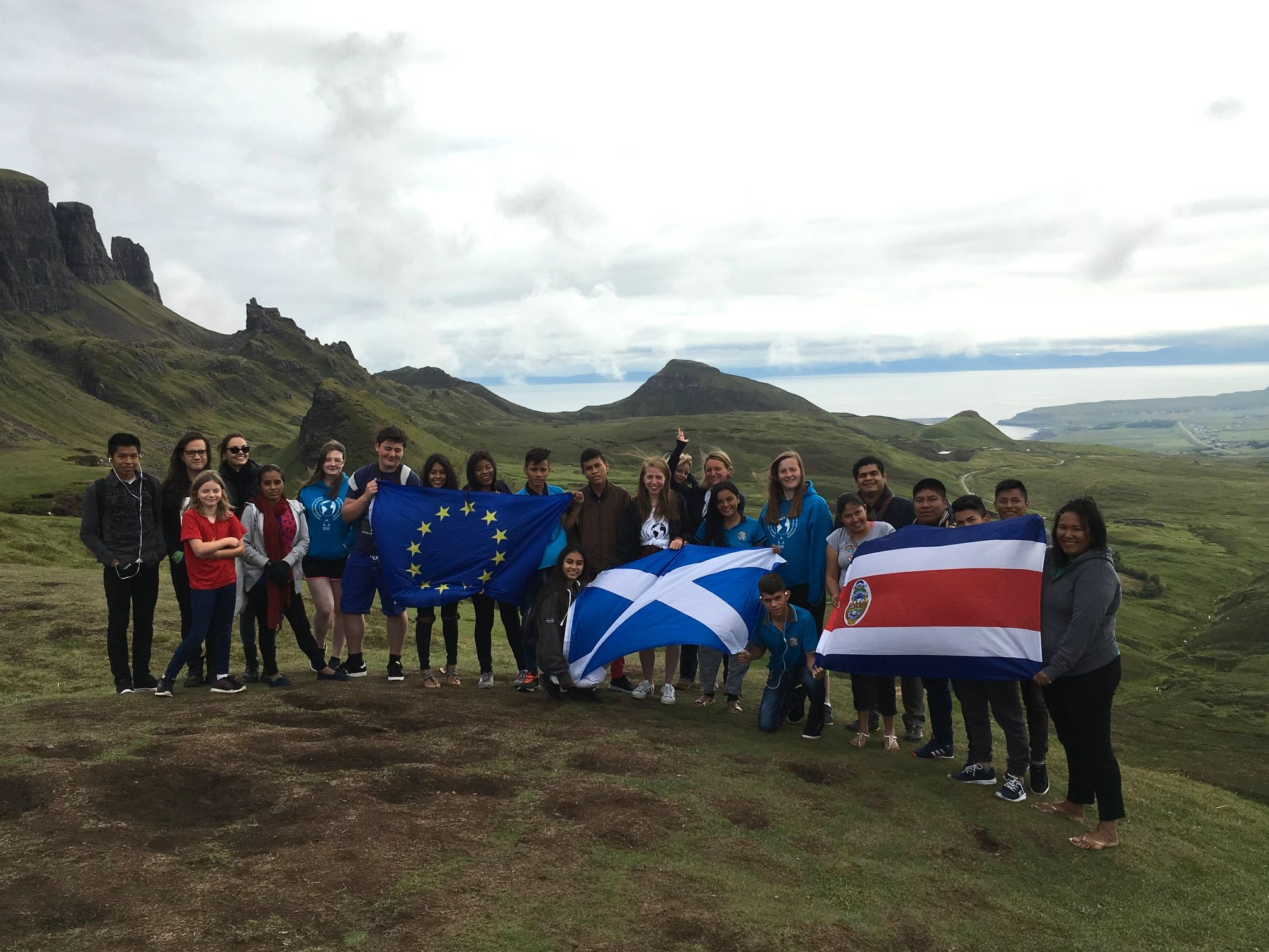 Participants from the Bi-Regional Youth Exchange on the Isle of Skye, July 2018, holding flags of Scotland, Costa Rica and the European Union