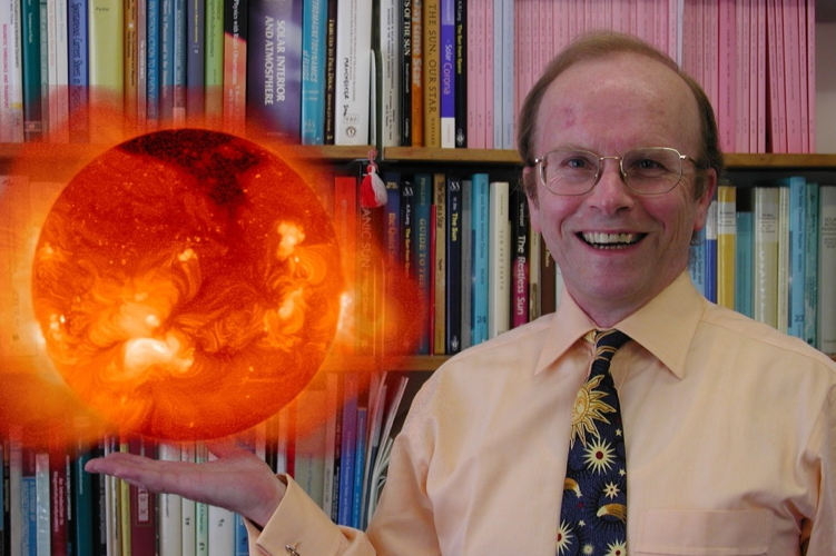 Photo of Professor Eric Priest that looks like he is holding the sun