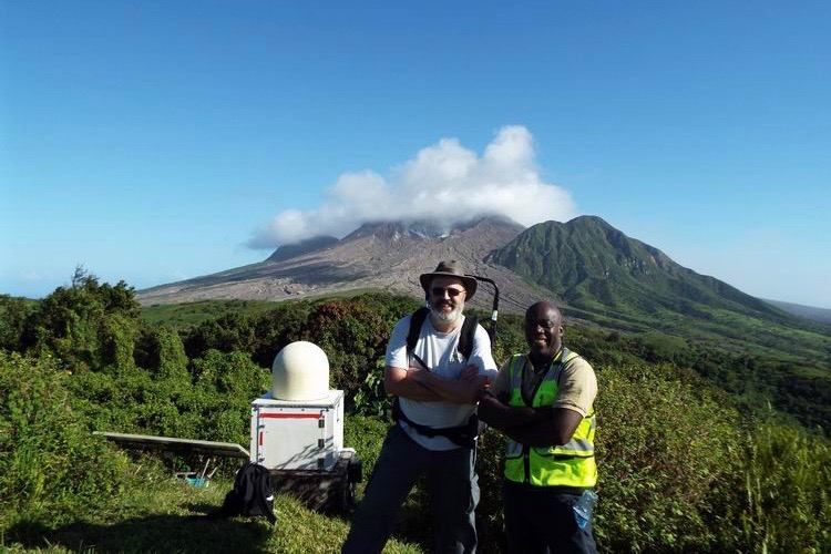 Two men standing besides the radar with a volcano in the background.