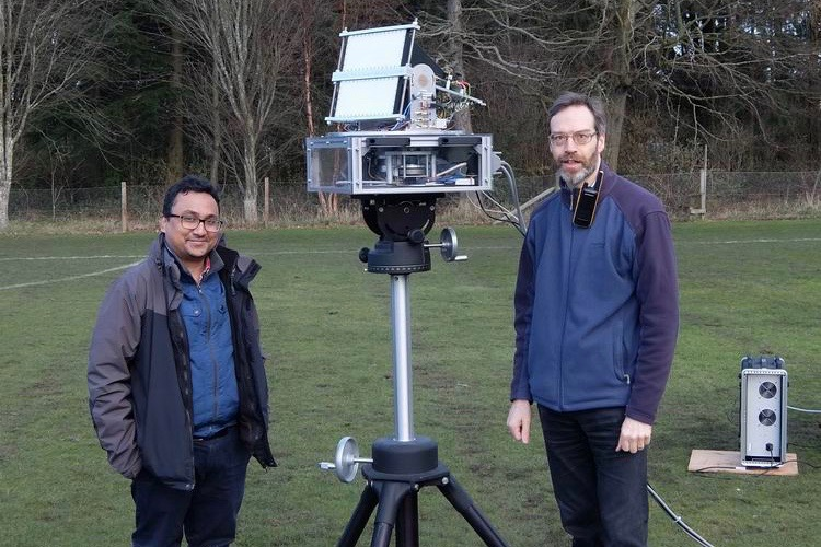 Two scientists standing outside with a radar monted in a tripod.