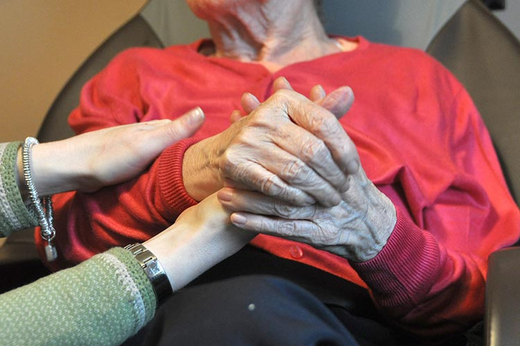 researcher holding hands with dementia patient
