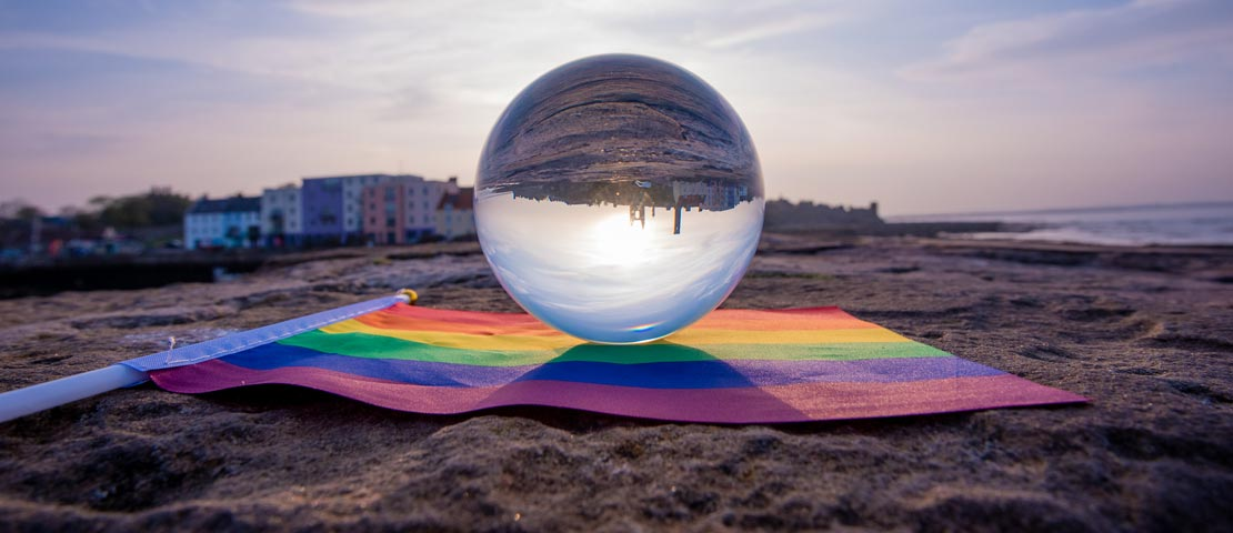 Crystal ball reflecting St Andrews harbour and LGBT flag