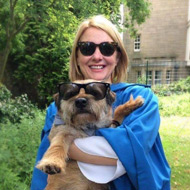 Dr Maggie Ellis holding a dog.  Both wearing sunglasses.