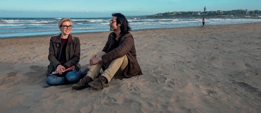 Postgraduate students sitting on a beach in St Andrews
