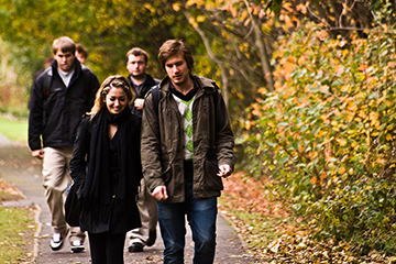Students walking down an autumnal path