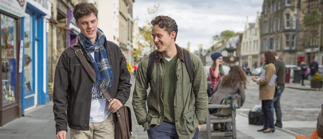Two young men walking through St Andrews