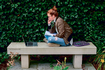 A student sitting on a bench and working on a laptop