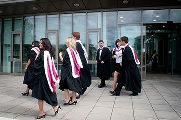 Graduates walking by the library building