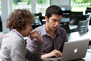 Two students working together on a laptop