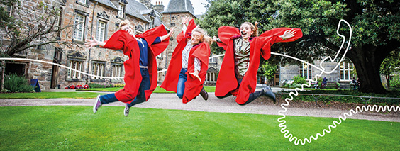 students in red gowns jumping