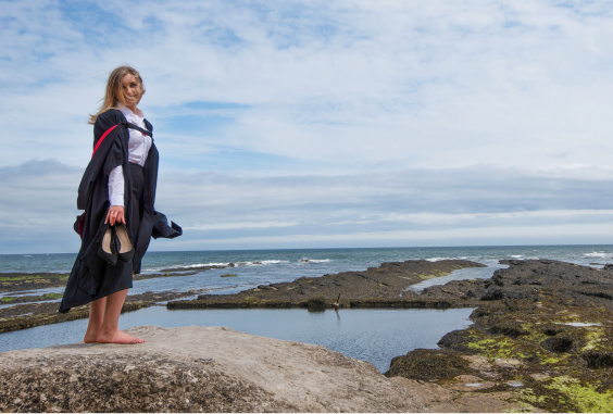 female student in robes standing on rocks