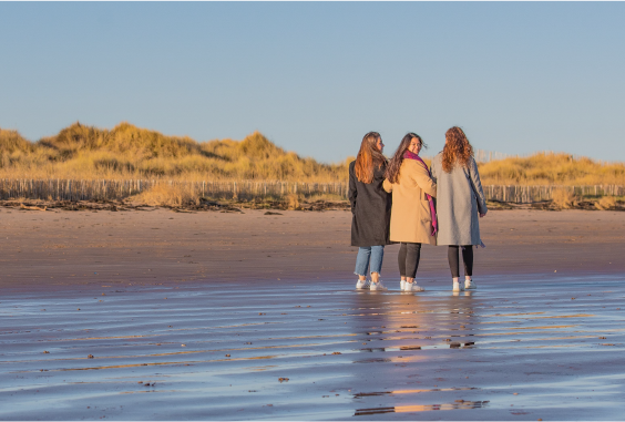 three female students on beach