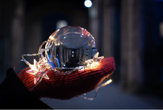 A Christmas bauble held in a gloved hand