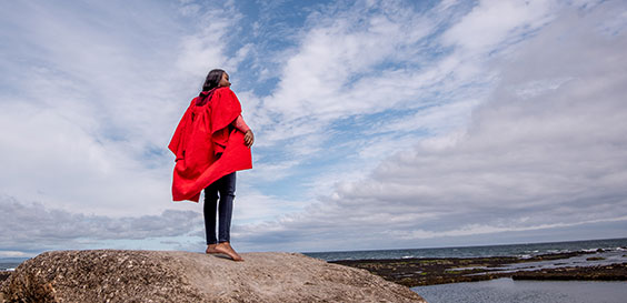 student in red gown on rock