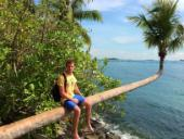 Photo of study abroad student Dylan sitting on a palm tree